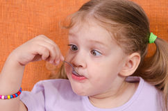 Funny girl squinted with his spoon in mouth. Three year old girl with pleasure and humor eats honey spoon sitting on the couch Stock Images