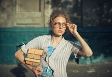 Funny girl student with books in glasses and a vintage dress Royalty Free Stock Images