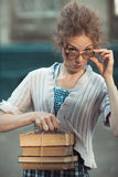 Funny girl student with books in glasses and a vintage dress Royalty Free Stock Photos