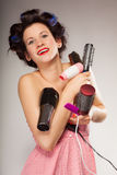 Funny girl styling hair holds many accessories Royalty Free Stock Images