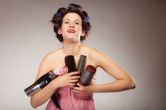 Funny girl styling hair holds many accessories. Young woman preparing for date having fun, cute girl with curlers styling hair with many accessories comb brush Royalty Free Stock Image