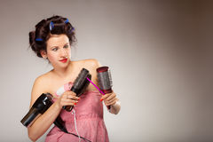 Funny girl styling hair holds many accessories Royalty Free Stock Photos
