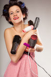 Funny girl styling hair holds many accessories. Young woman preparing for date having fun, cute girl with curlers styling hair with many accessories comb brush Stock Photos