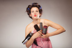 Funny girl styling hair holds many accessories Stock Images