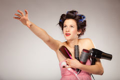 Funny girl styling hair holds many accessories Stock Photography