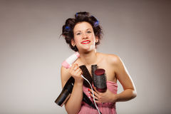 Funny girl styling hair holds many accessories. Young woman preparing for date having fun, cute girl with curlers styling hair with many accessories comb brush Stock Images