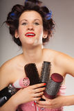 Funny girl styling hair holds many accessories. Young woman preparing for date having fun, cute girl with curlers styling hair with many accessories comb brush Stock Image