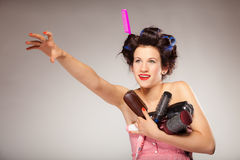 Funny girl styling hair holds many accessories Royalty Free Stock Photo