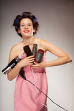 Funny girl styling hair holds many accessories. Young woman preparing for date having fun, cute girl with curlers styling hair with many accessories comb brush Royalty Free Stock Photography