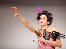 Funny girl styling hair holds many accessories. Young woman preparing for date having fun, cute girl with curlers styling hair with many accessories comb brush Royalty Free Stock Images