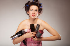 Funny girl styling hair holds many accessories. Young woman preparing for date having fun, cute girl with curlers styling hair with many accessories comb brush Stock Photo