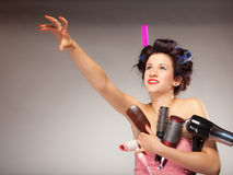 Funny girl styling hair holds many accessories. Young woman preparing for date having fun, cute girl with curlers styling hair with many accessories comb brush Stock Photography