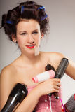 Funny girl styling hair holds many accessories. Young woman preparing for date having fun, cute girl with curlers styling hair with many accessories comb brush Royalty Free Stock Photos