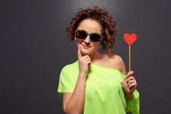 Funny girl in sunglasses holding small heart Royalty Free Stock Photo