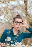 Funny Girl Surrounded by Blossoming Trees Afraid of Allergies Royalty Free Stock Photos