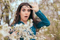 Funny Girl Surrounded by Blossoming Trees Afraid of Allergies. Circumspect woman analyzing effects of spring blooming nature on her health Royalty Free Stock Image