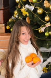 Funny girl with tangerines in christmas interior Stock Photography