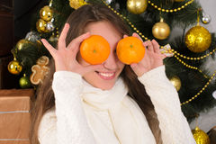 Funny girl with tangerines in christmas interior Stock Photos