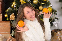 Funny girl with tangerines in christmas interior Royalty Free Stock Photo