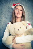Funny girl with teddy bear shows tongue. Royalty Free Stock Photos