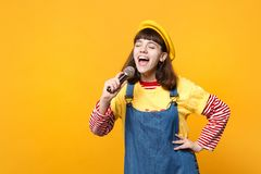 Funny girl teenager in french beret, denim sundress keeping eyes closed, sing song in microphone isolated on yellow stock images