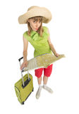 Funny girl tourist with bag finds route by map. Royalty Free Stock Photo