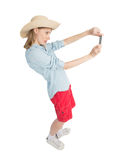 Funny girl tourist in straw hat makes picture. Royalty Free Stock Photography