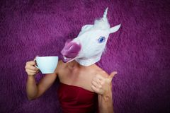 Funny girl unicorn drinks tea and shows thumbs up gesture. Freaky young woman in comical mask stands on the purple background. Portrait of unusual lady in red stock images