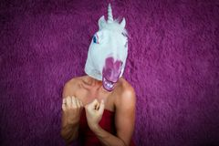 Funny girl unicorn ready to fight and clenches fists. Freaky young woman. In comical mask stands on the purple background. Portrait of unusual lady in red dress royalty free stock image