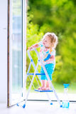 Funny girl washing a window Stock Photography