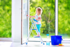 Funny girl washing a window in white room Royalty Free Stock Photography