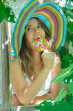 Funny girl wearing a colorful hat with lollipop in window with grape leaves Royalty Free Stock Images