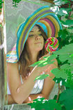 Funny girl wearing a colorful hat with lollipop in window with grape leaves Stock Photo