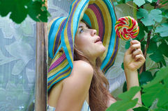 Funny girl wearing a colorful hat with lollipop in window with grape leaves Royalty Free Stock Photography