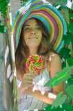 Funny girl wearing a colorful hat with lollipop in window with grape leaves Royalty Free Stock Image