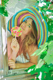Funny girl wearing a colorful hat with lollipop in window with grape leaves Stock Images