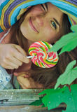 Funny girl wearing a colorful hat with lollipop in window with grape leaves Stock Image