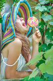 Funny girl wearing a colorful hat with lollipop in window with grape leaves Royalty Free Stock Photo