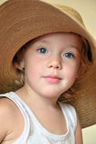 Funny girl wearing huge hat Royalty Free Stock Image