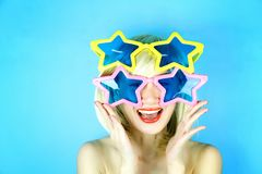 Funny girl wearing star shaped glasses, Playful girl with funny glasses. Stock Photo