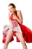 Funny girl whos skirt blows up showing her panties. Girl in red gala dress making fun with a ventilator Stock Photos