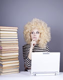 Funny girl in wig with notebook and books. Stock Photo