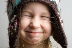 Funny girl in winter hat. Closeup funny portrait of little girl in winter hat stock photography