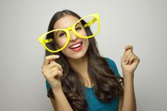 Funny girl with yellow big glasses dancing on gray background. Young woman have fun for the New year. Funny girl with yellow big glasses dancing on gray Royalty Free Stock Photo