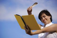 Funny girl with a yellow notebook. In a blue sky Stock Image