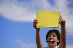 Funny girl with a yellow notebook. In a blue sky Stock Photos