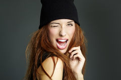 Funny Girl. Young woman in black beanie winking and smiling Royalty Free Stock Photography