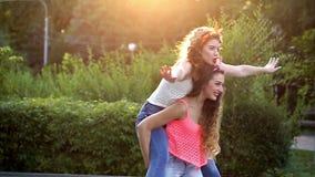 Funny girlfriend. Girl holds the girlfriend on piggyback. stock video