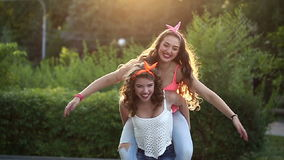 Funny girlfriend. Girl holds the girlfriend on piggyback. stock footage