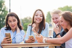 Funny girlfriends use a smartphone and laugh royalty free stock images